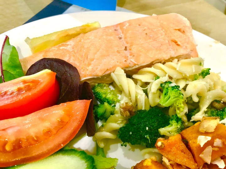 A close up photograph of a plate of salmon salad, there's a filet with big tomatoes and a broccoli pasta and chunks of sweet potato.