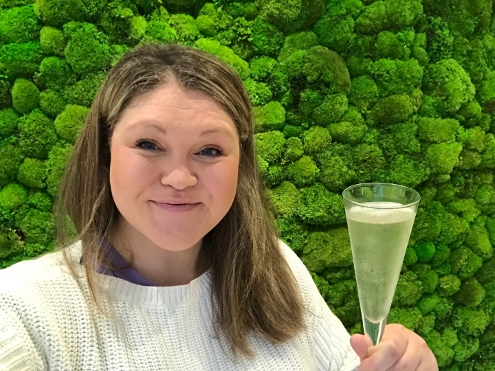 Bex posing in front of the spa's big green moss wall, she's holding a glass of Prosecco and she's looking very relaxed.