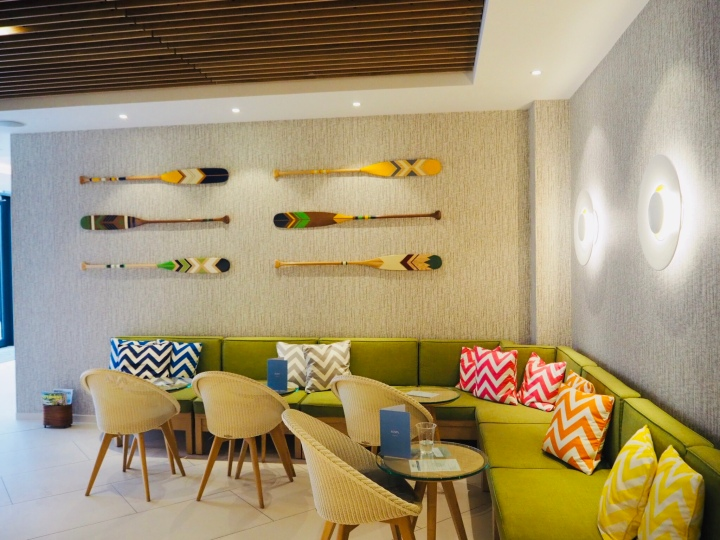 A picture of the corner of the spa's cafe, L shaped green sofas are covered in bright zig zag pattern pillows with small round tables and beige chairs. The walls are grey and six brightly coloured patterned paddles are hung on the wall in two sets of three.