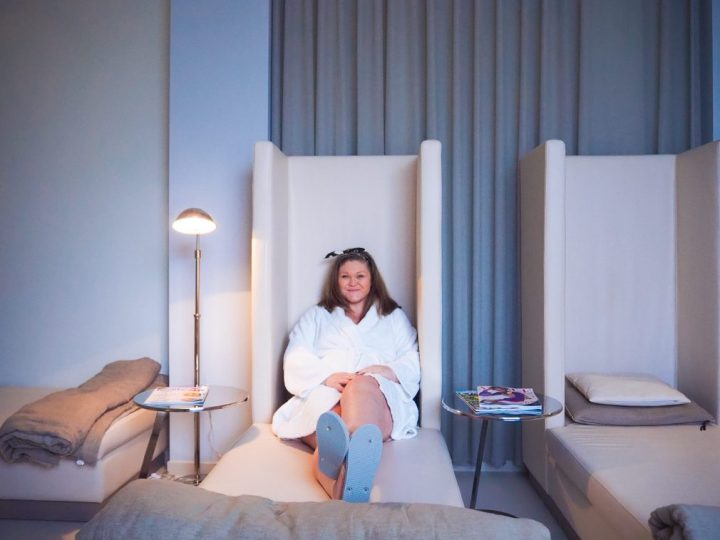 Bex sat on a comfy chaise lounge in the relaxation room of a spa. She's wearing a big white fluffy robe and looks relaxed.