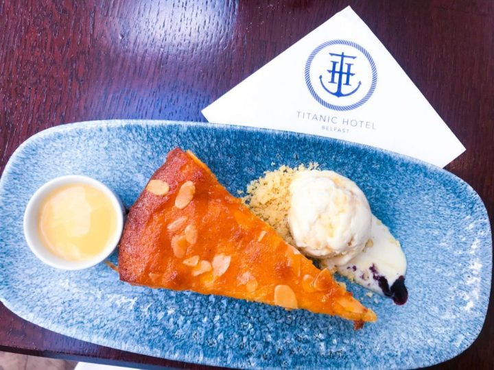 A slice of cherry bakewell cake with honeycomb ice cream, it's an aerial photograph with a napkin on the table with he Titanic Hotel's logo on it.