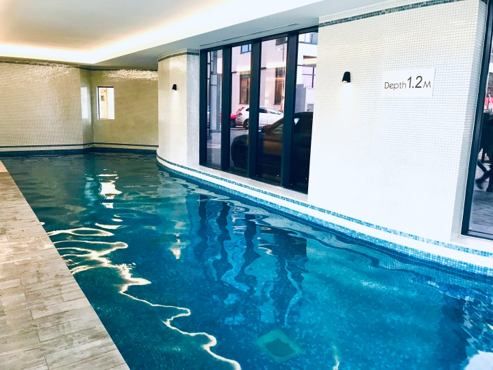The hotel's long swimming pool, the walls are covered in tiny white pearl mosaic tiles.