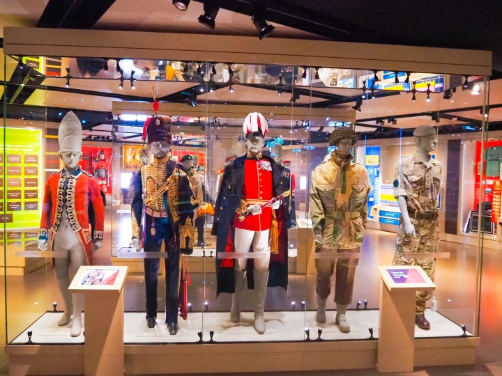 Five different Army uniforms from a long time period, old to modern.