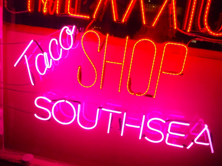 Pink neon lights saying Taco Shop Southsea