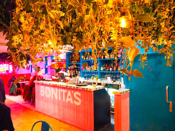 The bar area of Bonita's is long and bright pink with lots of plants hanging over the top of it.