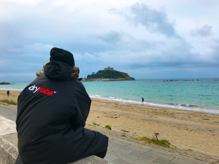 Bex rapped up warm sat on the beach looking out at the island St. Michael's Mount is on. The skies are dark as the weather wasn't good.
