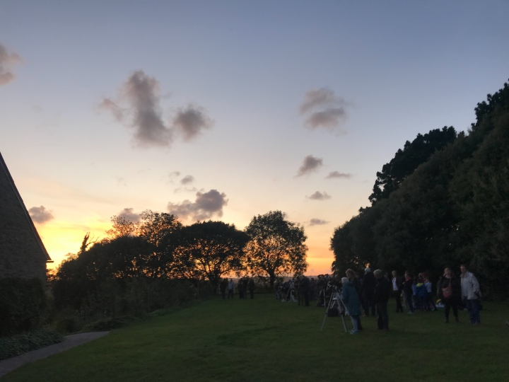 The sunsets over the green where the telescopes have been set up and people are waiting to stargaze